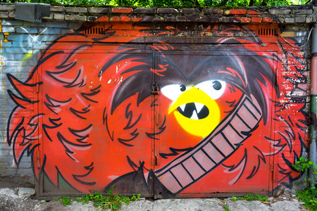 MOSCOW, RUSSIA - JUNE 06, 2015: Street art or graffiti by unidentified artist in the garage doors. The image of angry red bird.