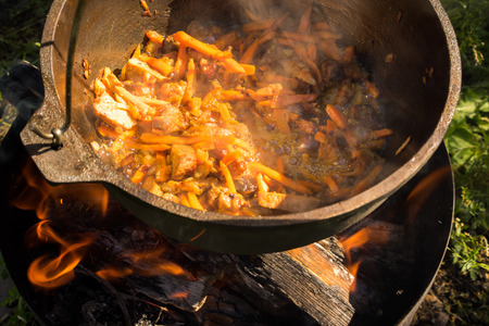 hot pot: close up view of cooking meat, onion and carrot in a metal pan in a campfire Stock Photo