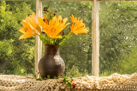 good mood: Asiatic Hybrids orange lilies bouquet on a window sill in a sunny rainy day. Good mood emotions of orange color.