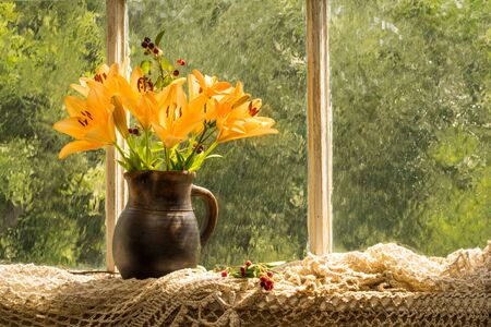 window sill: Asiatic Hybrids orange lilies bouquet on a window sill in a sunny rainy day. Good mood emotions of orange color.