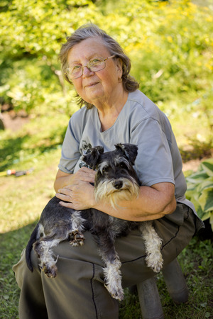 senior 70s woman holding her black and silver mini schnauzer dog sitting outdoor Stockfoto