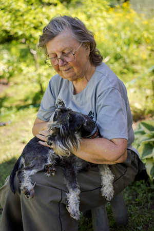 70's: senior 70s woman holding her black and silver mini schnauzer dog sitting outdoor Stock Photo