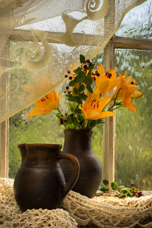 purdah: orange lily bouquet on a window sill Stock Photo
