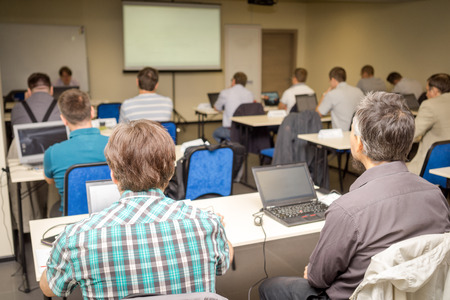 office training: Rear view of people attentively listening to teacher in the classroom