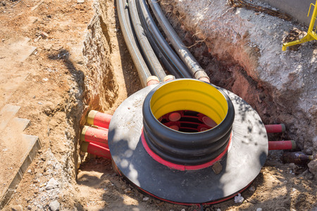 fibres: Excavation pit, electrical cables and optical fibres in the digging on a construction site