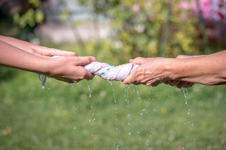 wor: Hands squeeze wet fabric on a grass background