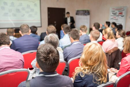 back screen: The audience listens to the acting in a conference hall. Seminar, Classroom, Adult. Stock Photo