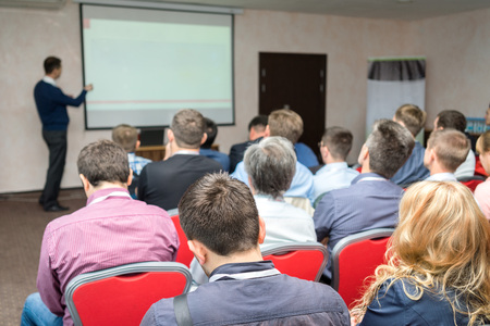 conference audience: people sitting rear at the business training and lecturer near the whiteboard pointing at the screen