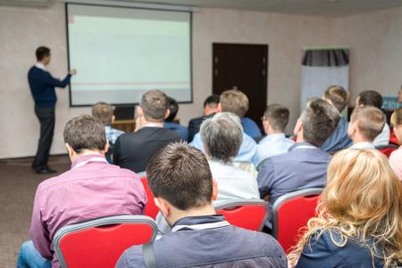 konferencia közönség: ember ül hátul az üzleti képzés és oktatói mellett a táblára mutatva a képernyőn Stock fotó