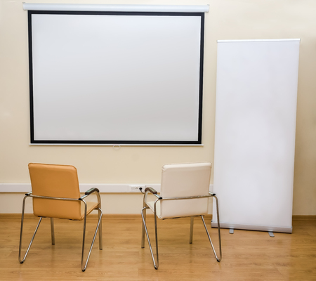two chairs: Blank white screen and roll-up banner and two chairs Stock Photo