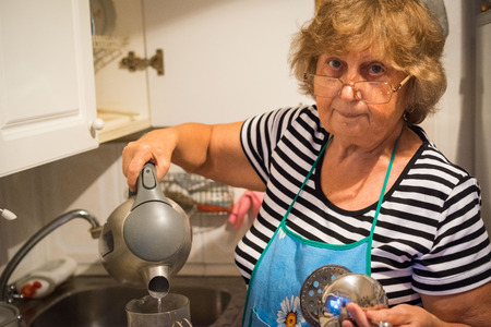 Retired Senior Woman In Kitchen Making Hot Drink Stockfoto
