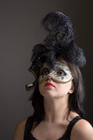 prideful: closeup portrait of young girl in black venetian mask. Stock Photo