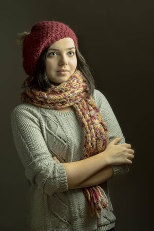 to fold one's arms: Close up portrait of a smiling young woman wearing beret hat and scarf posing with arms crossed on dark grey background Stock Photo