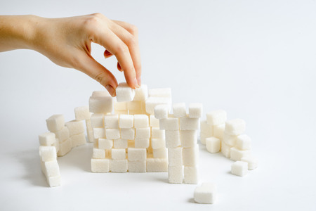 adding sugar: Female hand holding cube of sugar and building some tower and hardle of the fortress. Food concept,