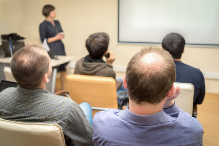 Back view of an adult students audience listening the presentation of a woman teacher near the screen