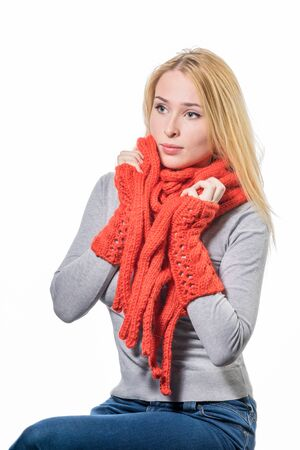 warmly: Cheerful blonde woman wrapped up warmly in a red wool winter scarf isolated on white