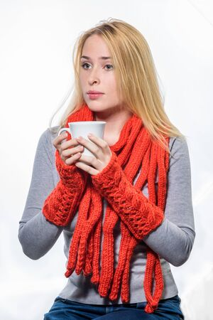 tea hot drink: Portrait of a young woman in red scarf and mittens holding cup with coffee or tea isolated on a white background Stock Photo