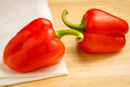 red peppers: Two red peppers on wooden table and white table cloth.
