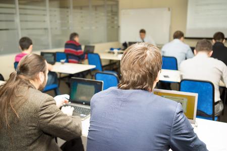 aula: detrás de la gente estudia o una conferencia o reunión o hacen taller en el aula con ordenadores portátiles en una sala de clase