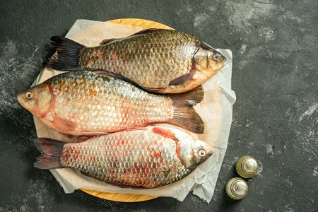 carassius gibelio: three raw carp fishes lying on wooden cutting board on a dark background with salt and pepper and copy space