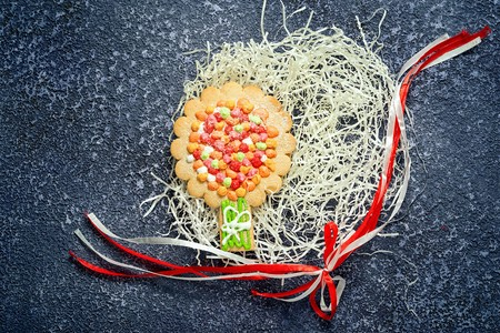 shredded paper: shredded paper nest with homemade tree cookie and ribbon bow on grey background. Stock Photo