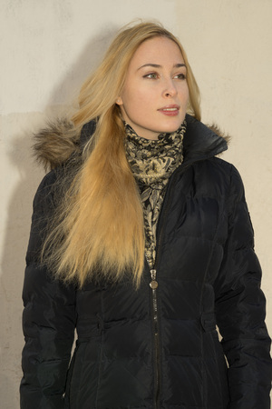 positiv: portrait of young positiv blonde caucasian woman in black parka near the wall Stock Photo