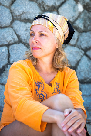 50s adult: portrait of the beautiful caucasian adult 50s woman with scarf tied on a head wearing orange blouse near the stone wall looking side