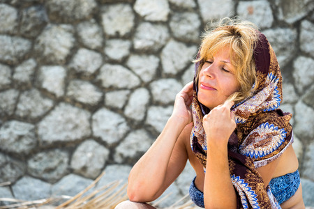 50s adult: Portrait of beautiful caucasian adult 50s woman relaxing. Scarf tied on a head with eyes closed near the stone wall Stock Photo