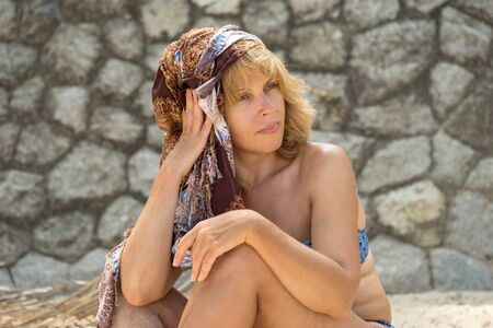 sunburnt: portrait of beautiful sunburnt adult caucasian woman in swimsuit and turban sitting on the beach against stone wall in the beach and lookind away Stock Photo