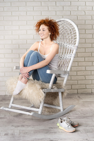 haircurlers: portrait of the young beautiful girl sitting in a rocking-chair against a brick wall Stock Photo