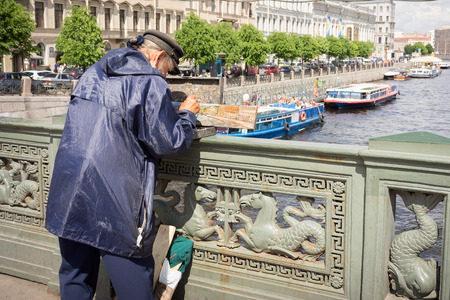 nicknamed: St Petersburg, Russia - May 26, 2016: Unidentified painter paints on Nevskom prospectus the boats in Fontanka river on Anichkov bridge. Saint-Petersburg has also been nicknamed  Venice of the North. Editorial