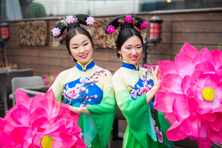 niñas chinas: two beautiful asian girls in traditional chinese blue and green dresses with umbrella in a form of lotus flowers