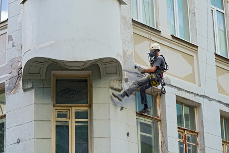 finishing: worker alpinist in a protective mask working with sander for smoothing wall surface of the building