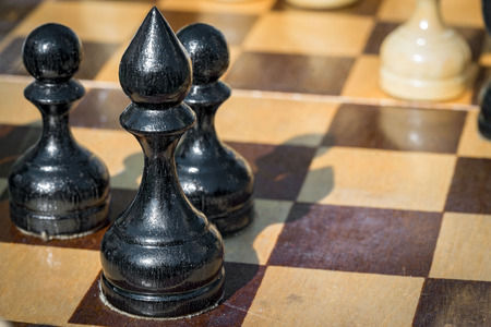 black bishop and pawns figures standing on chessboard Stock Photo