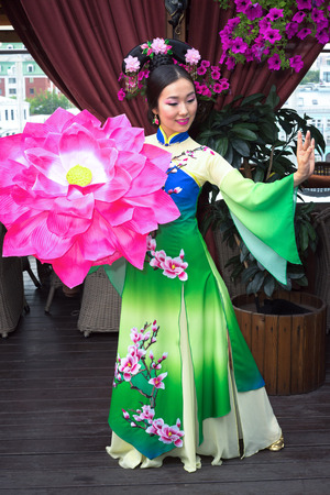 qipao: Beautiful Asian girl in traditional Chinese dress and floral parasol