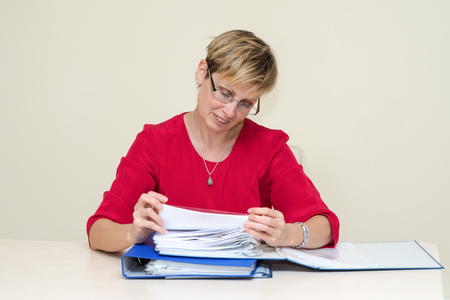 carefully: Business woman sitting at a table, carefully studying the documents folder Stock Photo