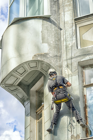 alpinist: worker alpinist in a protective mask working with sander for smoothing wall surface of the building