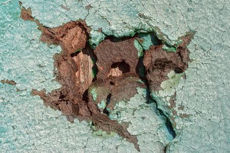 hardboard: hole in cracked hardboard wall, grunge wooden background