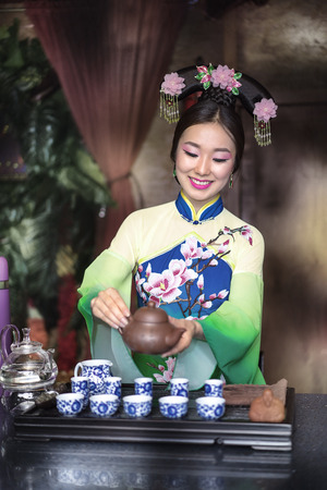 chinese tea ceremony: A young girl in a tradition dress holds a Chinese tea ceremony