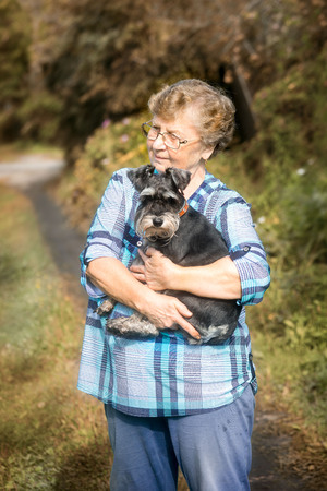 beautiful Senior smiling woman hugging her dog in the autumn outdoor