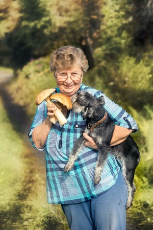 Portrait of the happy elderly woman with dog and two cepe mushrooms.