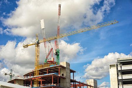 concrete commercial block: Crane and building construction site against blue sky