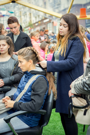 braiding: Moscow, Russia - September 11, 2016: Moscow City Day. Moscow residents and guests celebrate the 869 anniversary of the city. Hairdresser salon, braiding pigtails.
