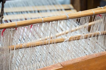 WEAVER: Weaving loom and shuttle on the warp.