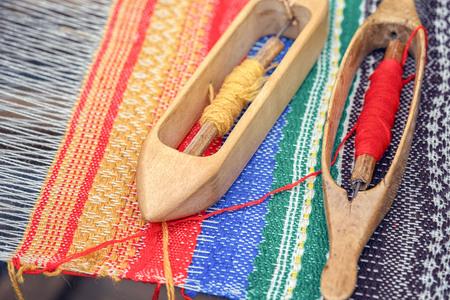loom: Weaving loom and shuttle on the warp.