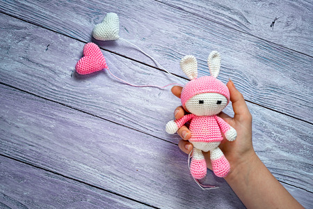 Childrens Hand Holding A Knitted Amigurumi Toy Rabbit And Two