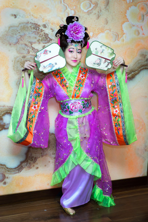 Beautiful Chinese young woman in Asian costume with two Asian fans