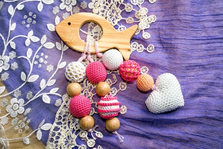 Wooden fish toy with crochet beads and heart on a rug background Stock Photo