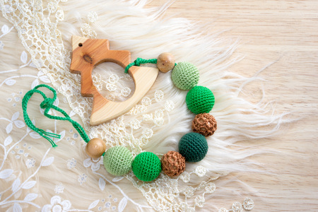 christmas tree ball: wooden toy Christmas tree with crocheted beads on a table with lace and fur Stock Photo