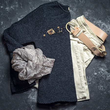 leathern: Flat lay top view outfit of casual woman. Black sweater, grey scarf, beige jeans and leather belt on a dark black background.